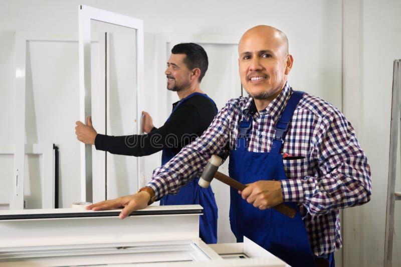 Arbete för två män på PVC-fönsterfabriken arkivbilder