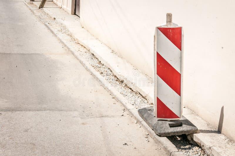 Arbete för vägtrafiktecken framåt med röda och vita barriärer på gatakonstruktionsplatsen i staden royaltyfria foton