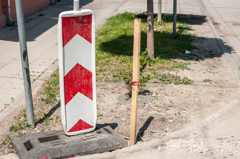 Arbete för vägtrafiktecken framåt med röda och vita barriärer på gatakonstruktionsplatsen i staden royaltyfri foto