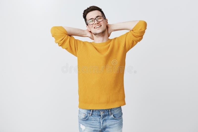 Arbete kan vänta Stående av den bekymmerslösa avkopplade och lata stiliga unga europeiska mannen i varm tröja som lägger det till royaltyfri bild