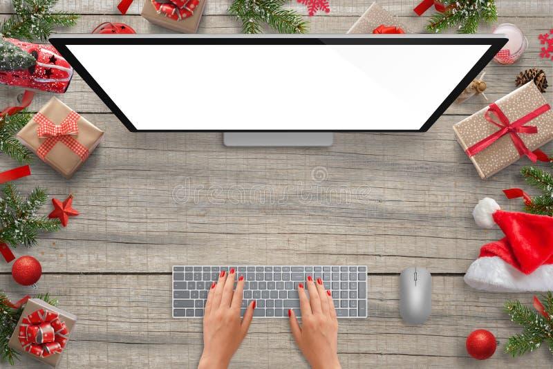 Arbete på datoren med den isolerade skärmen för modellpresentation Julplats med garneringar royaltyfria bilder