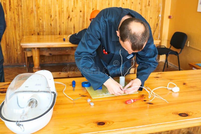 Arbeten för en elektriker för man samlar funktionsdugliga, den elektriska strömkretsen av en stor vit gatalampa med trådar, en re fotografering för bildbyråer