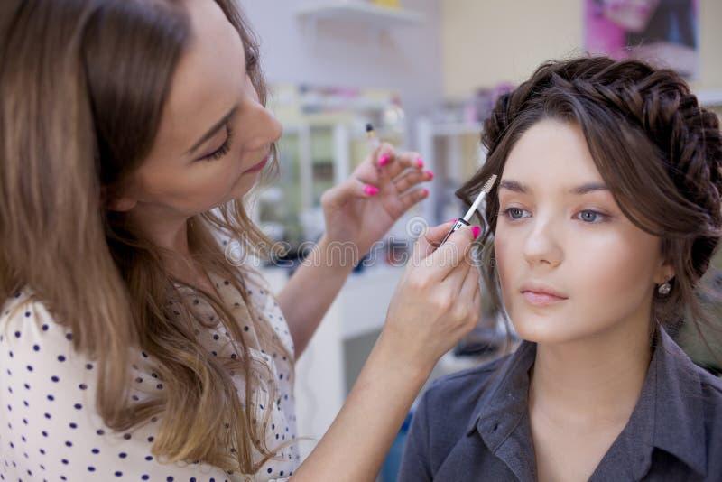 Arbetet av en yrkesmässig för Stylist för makeupkonstnär som konstnär makeup gör makeup och hår i en skönhetsalong arkivbild
