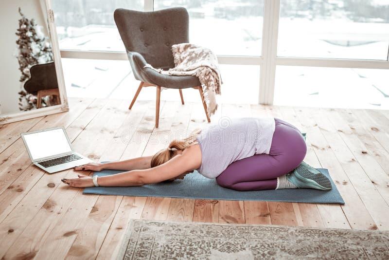 Arbetsam kvinna i violett damasker som sträcker alla kroppmuskler arkivfoto