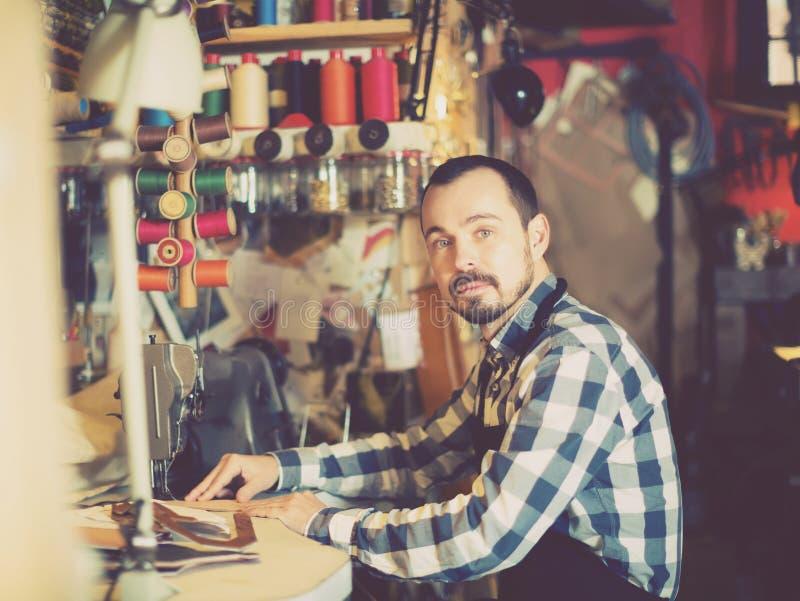 Arbetsam man som arbetar på häftklammer för bälte arkivbilder