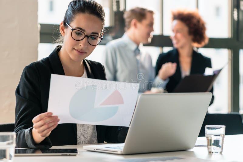 Arbetsam ung kvinna som analyserar information om affär arkivbild