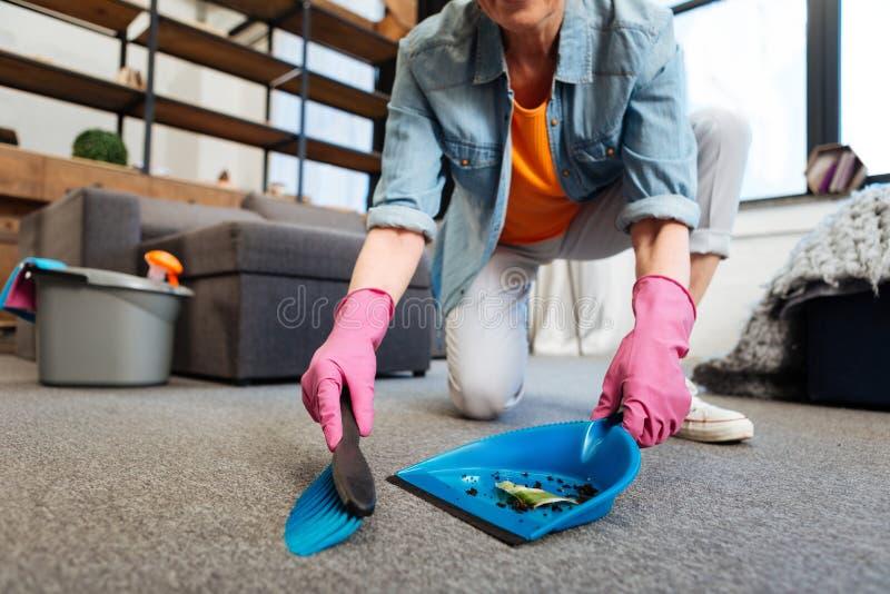 Arbetsamt rengöringsmedel som använder den blåa skopan och kvasten för att samla smuts arkivbilder