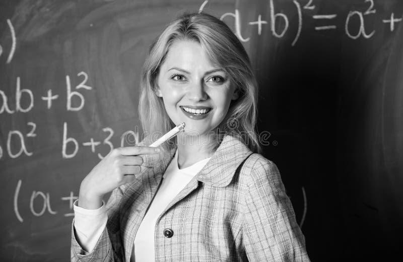 Arbetsförhållanden som presumtiva lärare måste betrakta Kvinna som ler bakgrund för svart tavla för utbildareklassrum arkivbild