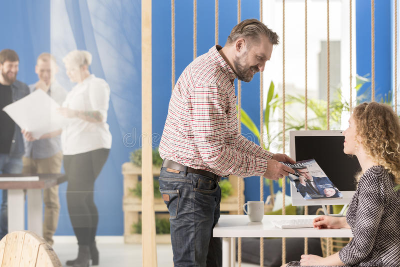 Arbetsgivare som visar en tidskrift arkivfoton