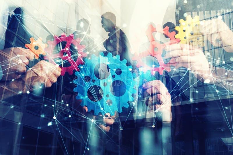 Arbetsgruppen av affärsmän finner överenskommelsen, genom att rymma ett stycke av kugghjulet i hand begrepp av teamwork och affär arkivbild