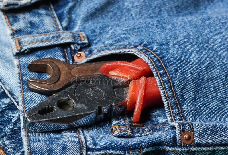 Arbetshjälpmedel i facket av jeans Plattång skiftnyckel, justerbar skiftnyckel royaltyfria bilder