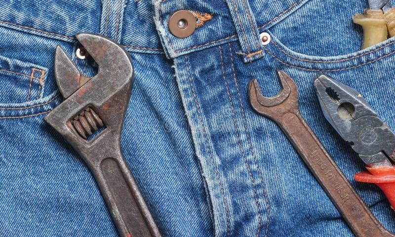 Arbetshjälpmedel på jeans Plattång skiftnyckel, justerbar skiftnyckel royaltyfria bilder
