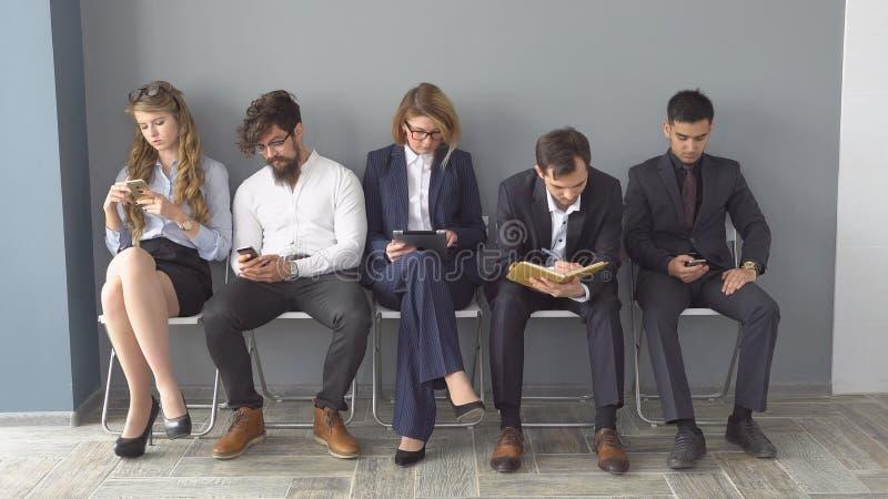 Arbetslöns förväntar intervjuer som sitter på stolar i hallet av en kontorsbyggnad arkivbild