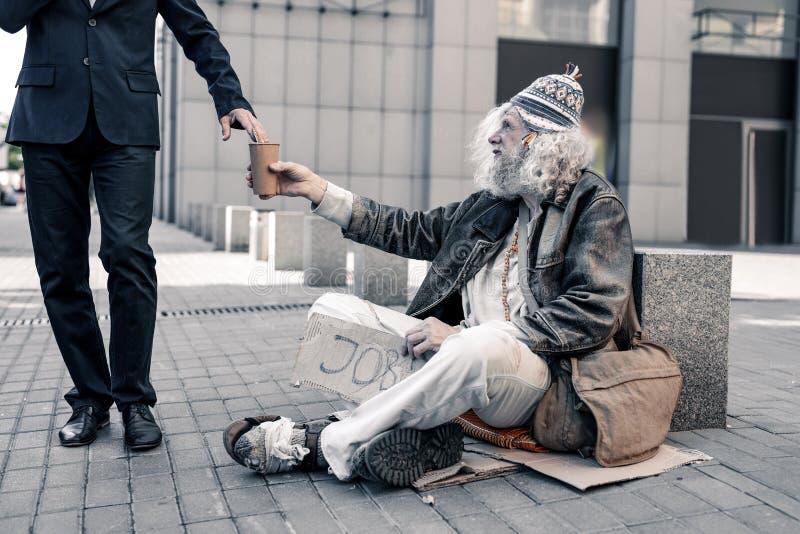 Arbetslös bedrövlig man som sitter på gatan i smutsiga filtar royaltyfria foton