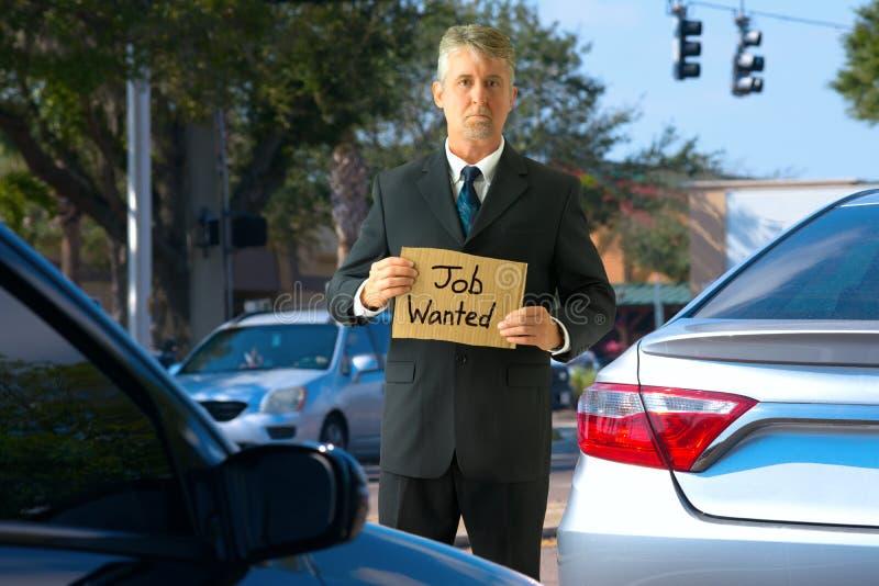 Arbetslös panhandlerman på trafikgenomskärningen med det Job Wanted tecknet arkivbild