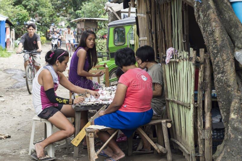 Arbetslösa mödrar spenderar tiddobbleri i en slumkvarterkraftfullgata royaltyfri bild