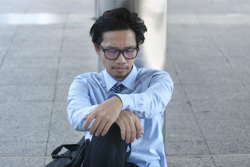Arbetslöst ungt asiatiskt affärsmansammanträde på golvet av trottoarkontoret Deprimerad arbetslöshetaffärsidé arkivbild