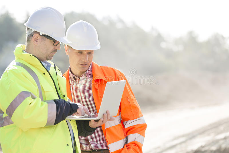 Arbetsledare som använder bärbara datorn på konstruktionsplatsen arkivfoton