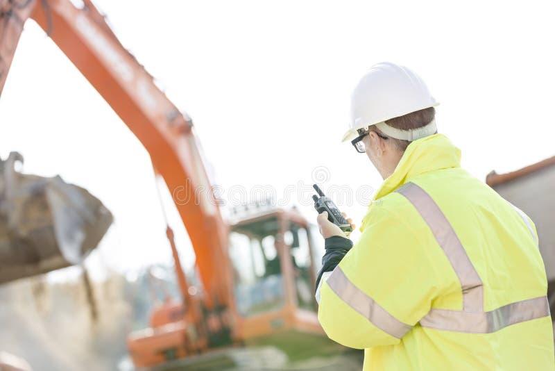 Arbetsledare som använder walkie-talkie på konstruktionsplatsen mot klar himmel arkivbilder