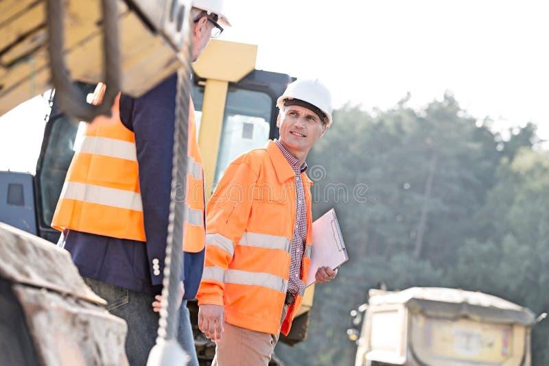Arbetsledare som diskuterar, medan gå på konstruktionsplatsen arkivbilder