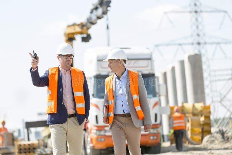 Arbetsledare som diskuterar på konstruktionsplatsen royaltyfri fotografi