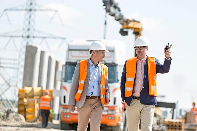 Arbetsledare som diskuterar på konstruktionsplatsen arkivfoton