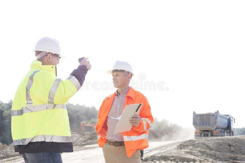 Arbetsledare som diskuterar på konstruktionsplatsen mot klar himmel arkivbild