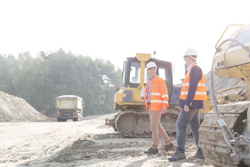 Arbetsledare som går på konstruktionsplatsen mot klar himmel arkivfoton