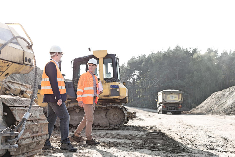 Arbetsledare som går på konstruktionsplatsen mot klar himmel fotografering för bildbyråer