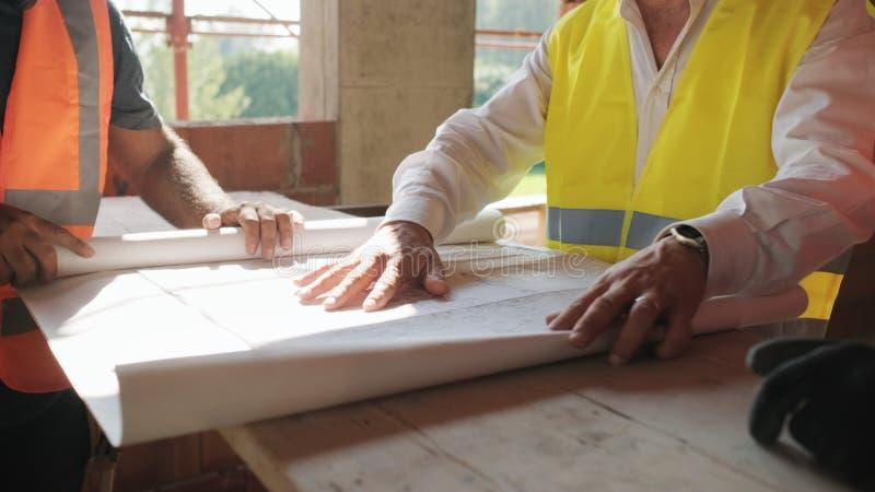 Arbetsledare som visar byggande plan till arbetare i nytt hus royaltyfri bild