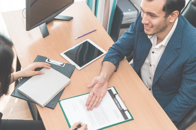 Arbetsledaren av personalresursen inviterar ny anställd att underteckna avtalet arkivbilder