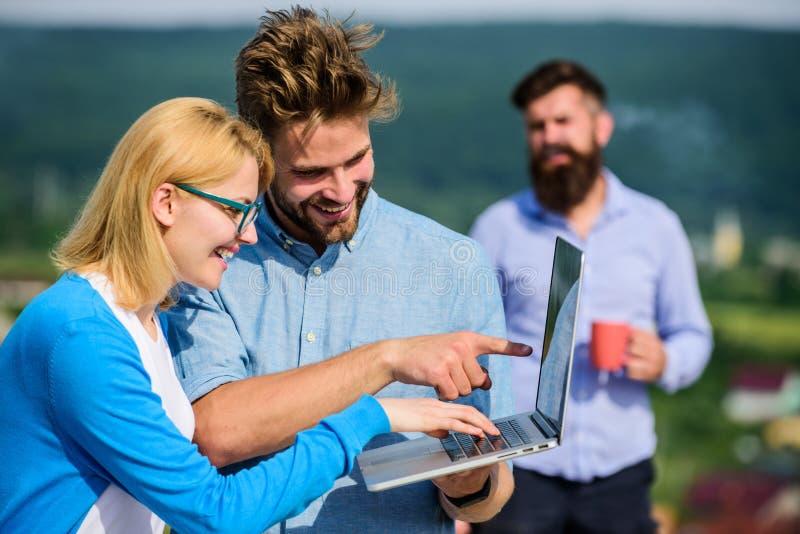 Arbetsnarkomanbegrepp Kollegor med bärbara datorn arbetar den utomhus- soliga dagen, naturbakgrund Paret arbetar illvilja av kaff arkivfoton