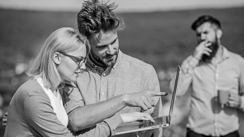 Arbetsnarkomanbegrepp Kollegor med bärbara datorn arbetar den utomhus- soliga dagen, naturbakgrund Paret arbetar illvilja av kaff royaltyfria foton