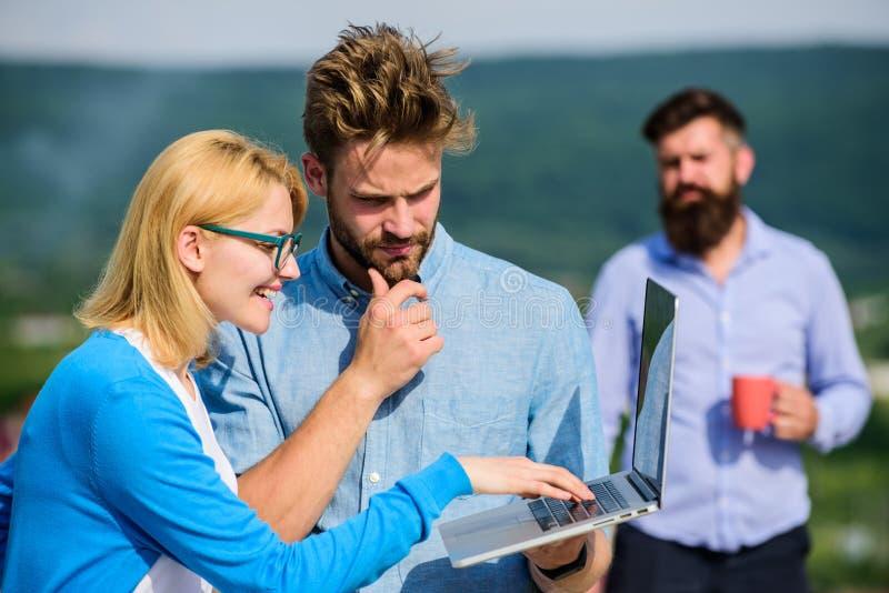 Arbetsnarkomanbegrepp Kollegor med bärbara datorn arbetar den utomhus- soliga dagen, naturbakgrund Kollegor som arbetar bärbara d royaltyfri fotografi
