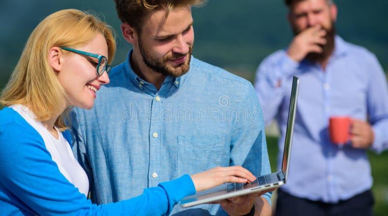 Arbetsnarkomanbegrepp Paret arbetar illvilja av kaffeavbrottet Kollegor med bärbara datorn arbetar den utomhus- soliga dagen, nat royaltyfri foto