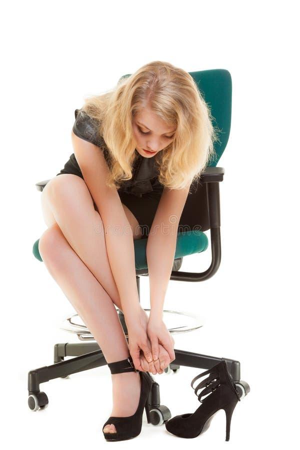 Arbetsnedläggelsen och foten smärtar. Affärskvinna på stol som tar av skor. fotografering för bildbyråer