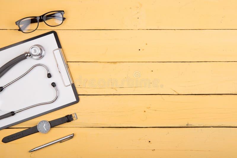 Arbetsplats av doktorn - stetoskop och andra tillf?rsel p? det gula tr?skrivbordet arkivfoto