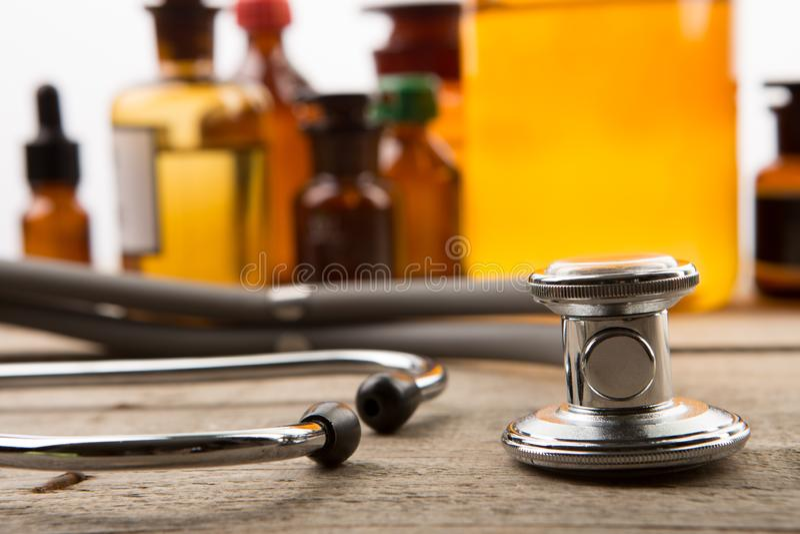 Arbetsplats av doktorn - stetoskop- och apotekflaskor p? tr?skrivbordet arkivbild