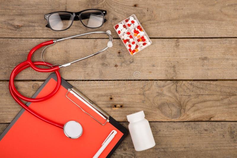 Arbetsplats av doktorn Stetoskop, skrivplatta, exponeringsglas och preventivpillerar på träskrivbordet fotografering för bildbyråer