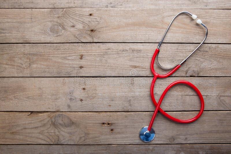 Arbetsplats av en doktor - stetoskop på träskrivbordet arkivbilder