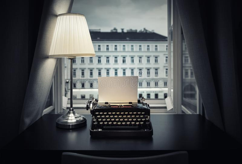 Arbetsplats av en författare, journalist, skapare En gammal skrivmaskin och en lampa på tabellen retro stil Begreppet på vetenska royaltyfri foto