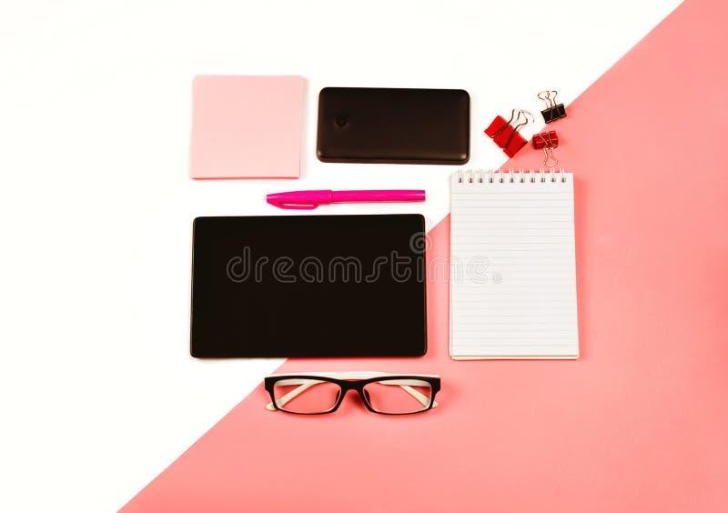 Arbetsplats för kvinna` s med den svarta minnestavlan, anteckningsboken, telefonen, exponeringsglas, rosa färgpappersanmärkningar fotografering för bildbyråer