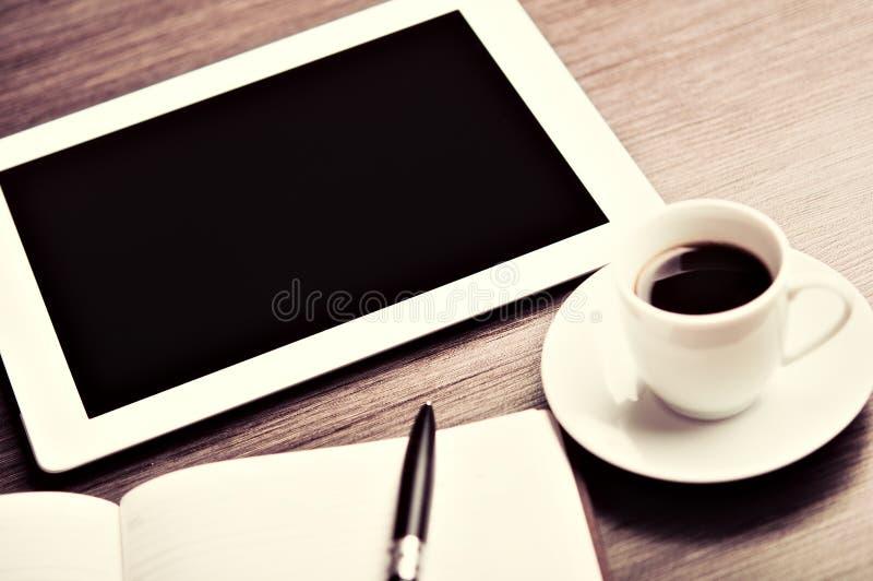 Arbetsplats kontorsskrivbord: kaffe och minnestavlaPC och anteckningsbok med p arkivbilder