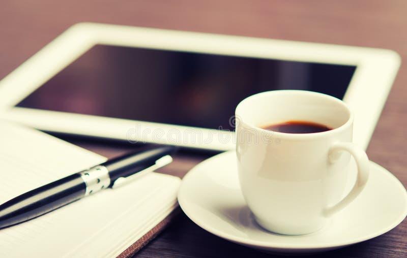 Arbetsplats kontorsskrivbord: kaffe och tabletPC och anteckningsbok med p royaltyfri bild