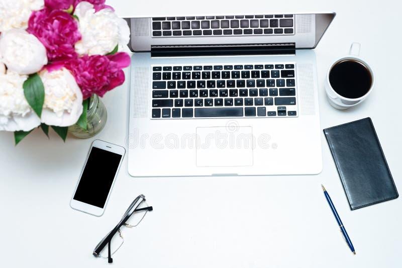 Arbetsplats med bärbara datorn, anteckningsboken, mobiltelefonen, exponeringsglas, pennan och rosa och vita pionblommor på den vi royaltyfria bilder