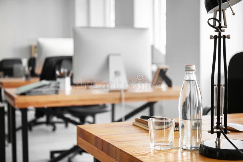 Arbetsplats med flaskan av vatten, lampan och anteckningsboken på tabellen i modernt kontor arkivfoto