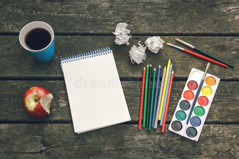 Arbetsplatsen av konstnären Never ger upp Koppen av varmt kaffe, notepad med det tomma arket av papper, färgade blyertspennor, må arkivbilder