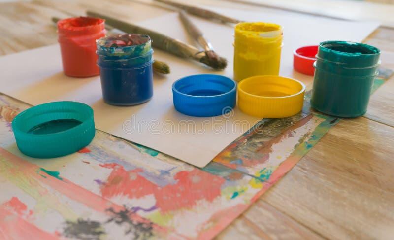 Arbetsplatsen av konstnären: vattenfärgmålarfärger, målarfärgborstar, ark av vitbok, färgpalett och oavslutad målning arkivbilder