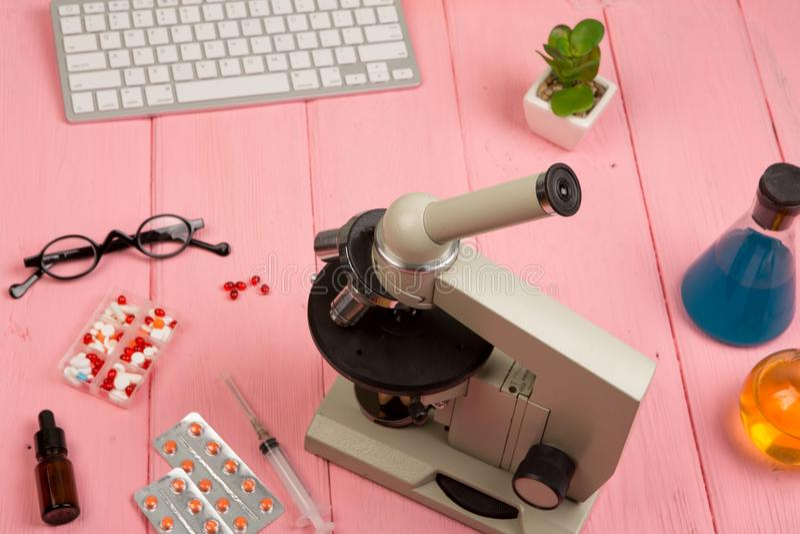 Arbetsplatsforskare/doktor - mikroskop, preventivpillerar, injektionsspruta, glasögon, kemiska flaskor med flytande på den rosa t arkivbilder