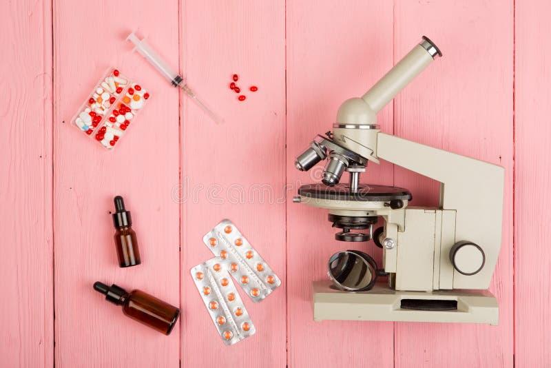 Arbetsplatsforskaredoktor - mikroskop, preventivpillerar, injektionsspruta på den rosa trätabellen arkivfoto